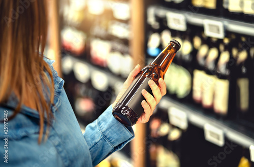 Foto op Canvas Bar Customer buying beer in liquor store. Lager, craft or wheat beer. IPA or pale ale. Woman at alcohol shelf. Drink section and aisle in supermarket. Lady holding bottle in hand. Drink business concept.