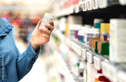 Photo sur Toile Pharmacie Customer in pharmacy holding medicine bottle. Woman reading the label text about medical information or side effects in drug store. Patient shopping pills for migraine or flu. Vitamin or zinc tablets.