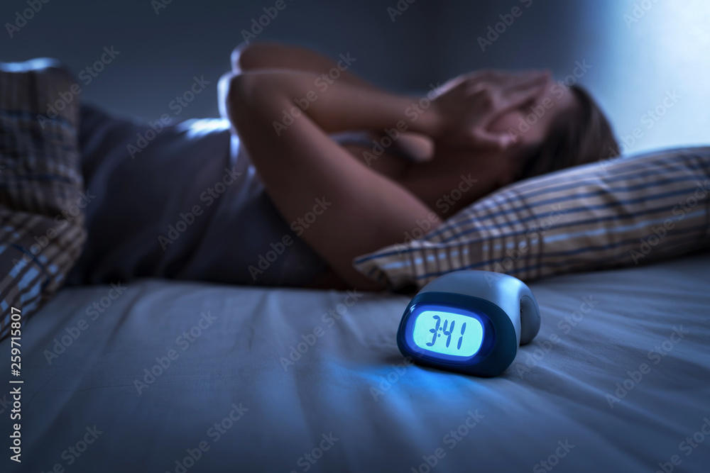 Fototapeta Sleepless woman suffering from insomnia, sleep apnea or stress. Tired and exhausted lady. Headache or migraine. Awake in the middle of the night. Frustrated person with problem. Alarm clock with time.