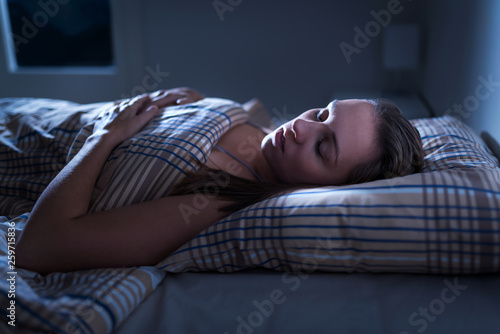 Photo  Calm and peaceful woman sleeping in bed in dark bedroom