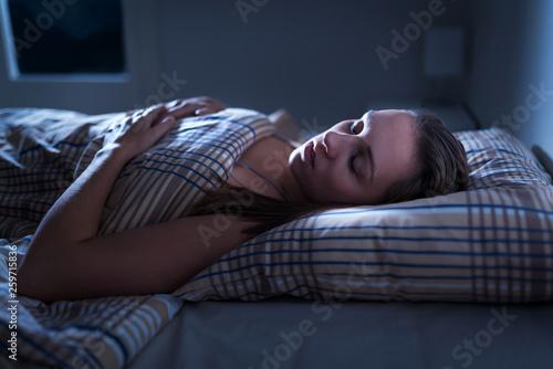 Calm and peaceful woman sleeping in bed in dark bedroom Wallpaper Mural