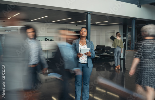 Fotomural Beautiful black african business woman standing in a busy lobby of an office loo