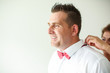 Handsome man prepared for wedding, girl fixing his bow tie
