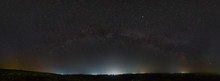 Stars Of The Milky Way In The Night Sky. Light Pollution From Street Lamps Above The Horizon.