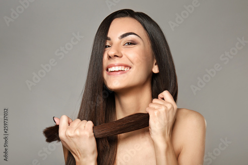 Portret piękna młoda kobieta z zdrowy długie włosy na szarym tle