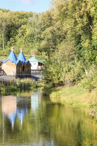 Fotografie, Tablou baptismal font on the Bank of the picturesque river Sunny summer day