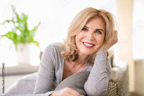 Fotografia  Portrait einer attraktiven älteren Frau zuhause auf der Couch, best ager