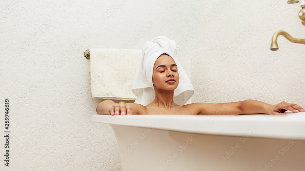 Fototapeta Woman with white towel on her head relaxing in bath with eyes closed