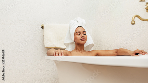 Foto Woman with white towel on her head relaxing in bath with eyes closed