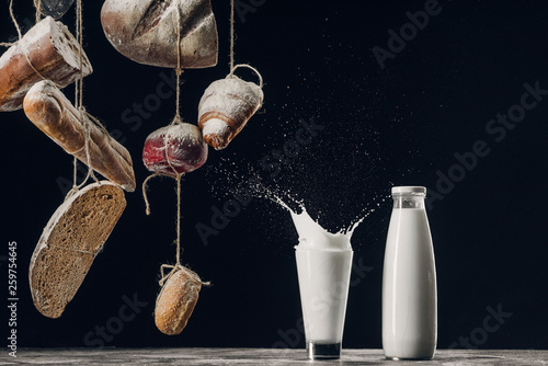 homemade bread hanging on ropes near splashing milk isolated on black