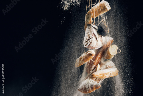 white flour falling at bread, baguettes and croissant on ropes on black background with copy space