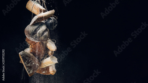 white flour falling at loaves of bread, baguettes and croissant on ropes on black background with copy space