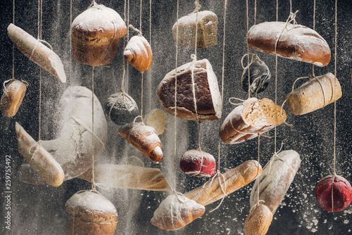 white flour falling at loaves of white and brown bread and pastry hanging on ropes