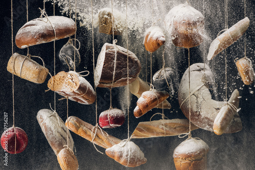 flour falling at loaves of white and brown bread and pastry hanging on ropes