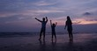SLOW MOTION, Silhouetted Asian family looking to sunset with happy emotion at Beach together. Family, Holiday and Travel concept.