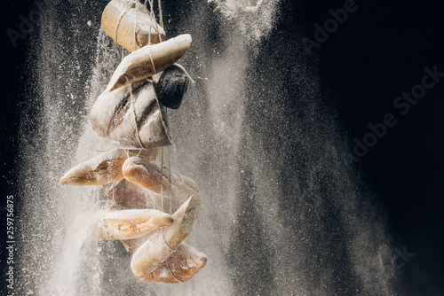 white flour falling at bread and baguettes on ropes on black background