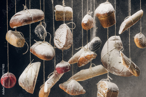 flour falling at fresh homemade bread and pastry hanging on ropes