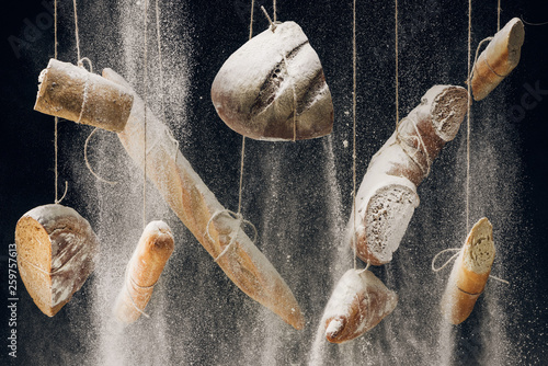 flour falling at bread, baguettes and croissant hanging on ropes on black background
