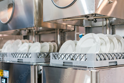 Photo  close up white plate on basket in automatic dishwasher machine for industrial