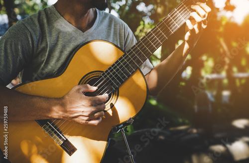 Foto  Man playing classic guitar at park