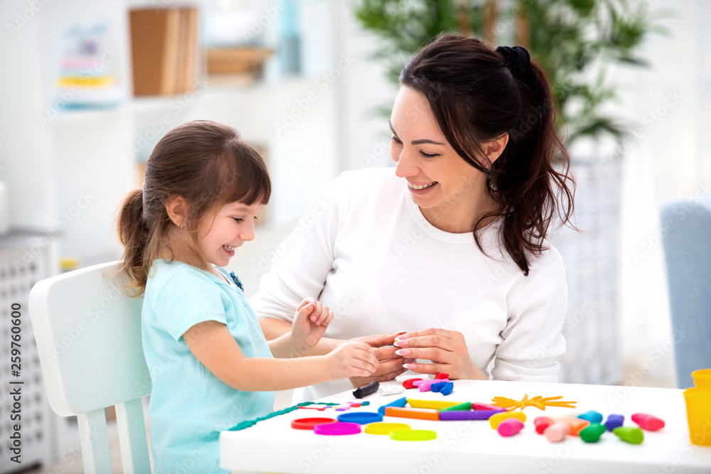 Fototapety, obrazy: Smiling mother helps a little daughter to sculpt figurines from plasticine. Children's creativity. Happy family