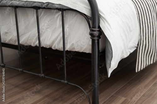 close up of bedding iron frame with white comfortable blanket and mattress