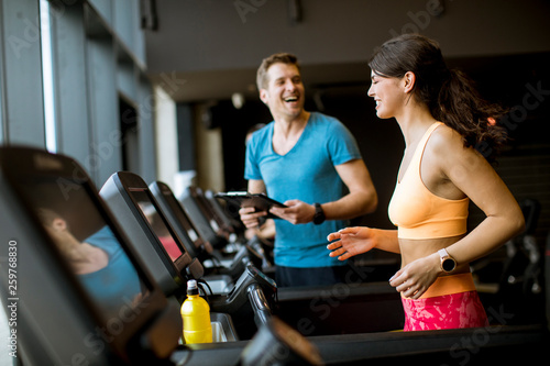 Poster Fitness Close up of woman with trainer working out on treadmill in gym