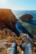 Crop legs of human sitting on top of stone hill near picturesque sea in sunny day in Cabo de Penas, Asturias, Spain