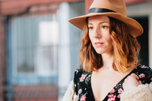 Positive Attractive Young Lady In Dress Wearing A Hat Looking Away