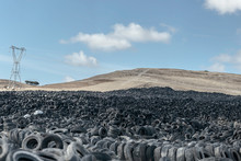 Huge Pile Of Old Auto Tires Between Meadow