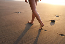 Crop Woman Strolling On Sand Of Beach