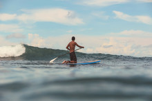 Back View Of Male Paddling On Surf Board Between Water Of Sea And Blue Sky On Bali, Indonesia
