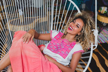 Beautiful Happy Black Young Woman Looking At Camera And Curly Hair Sitting On Chair In Mexico