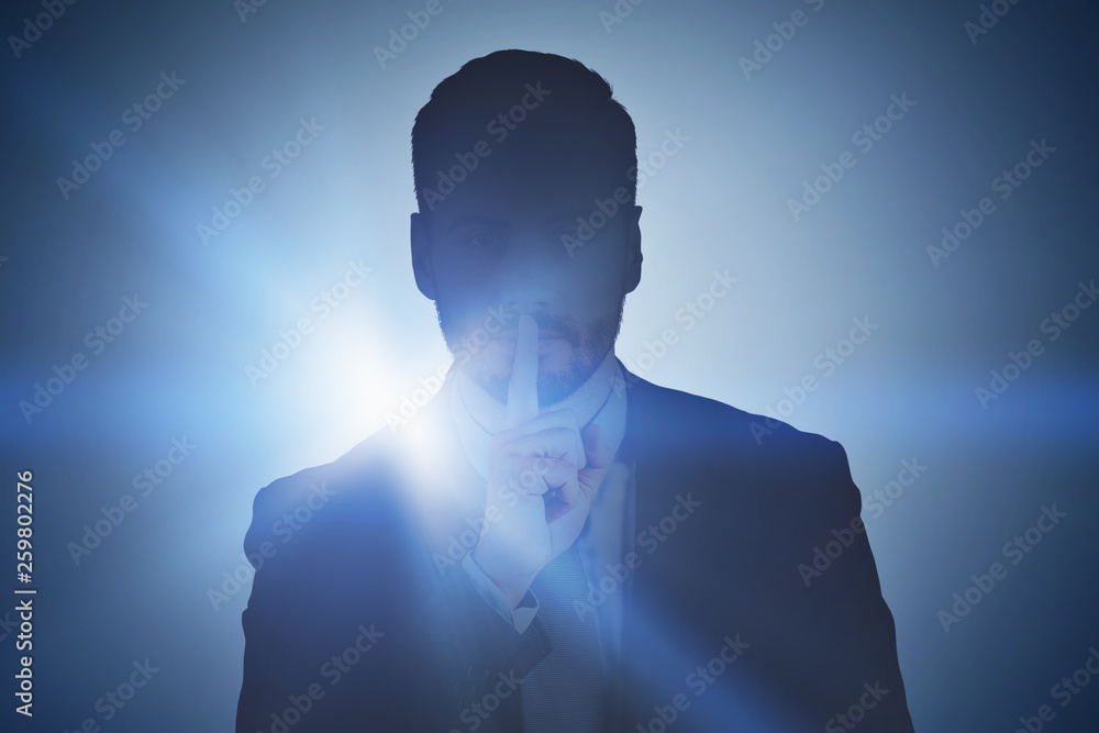 Fototapeta Businessman making hush sign, dark background