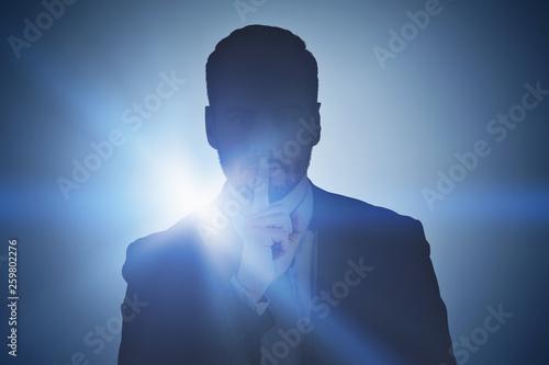 Obraz na plátně  Businessman making hush sign, dark background