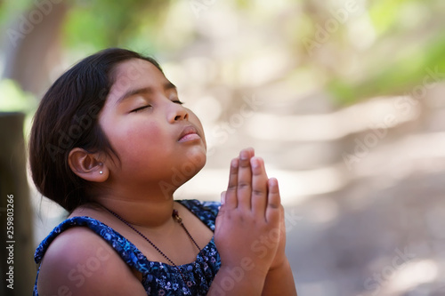 Fotografie, Tablou A young girl praying with hands together in reverence to God, wearing conservative clothing and in an outdoor setting