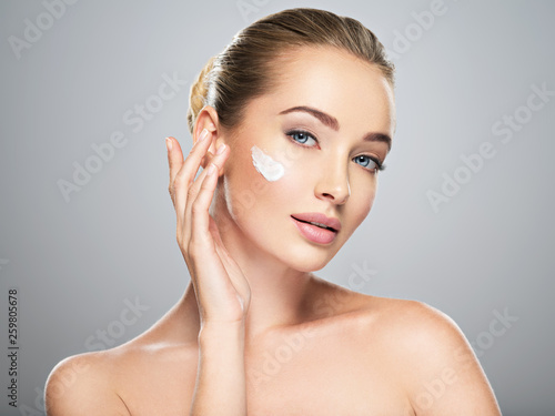 Fotografie, Obraz  woman gets cream in the face. Skin care concept.