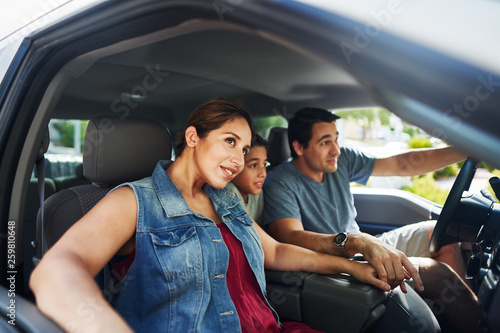 Fényképezés  hispanic family with mother, father and son sitting in truck looking outside