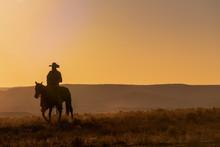 Lone Desert Cowboy Riding At Sunrise