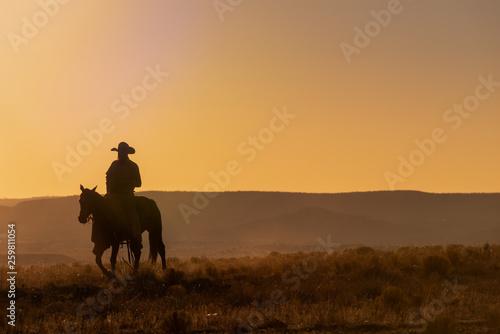 Valokuvatapetti Lone Desert Cowboy Riding At Sunrise