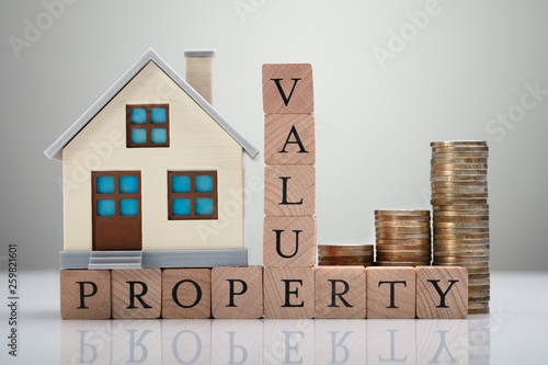Fototapeta Property Value Text With House Model And Stacked Coins obraz