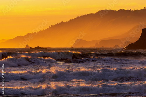 Fotografia  Dramatic Sunset with high tide on the beach with view of mountain range in San F