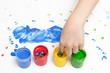 A child draws with colorful paint with his fingers on white paper.