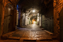 Narrow Cobbled Street In Old Medieval Town With Illuminated Houses And Pavement. Night Shot Of Side Passage In Some Ancient Castle. Closed Doors, Stone Paving And Hanging Lights In The Street.