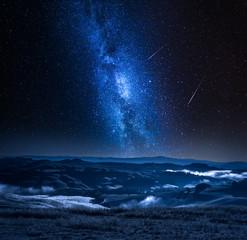 Droga Mleczna z spadającymi gwiazdami i mglistą doliną we Włoszech
