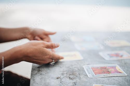 Fotografia Woman is reading Tarot cards at the beach