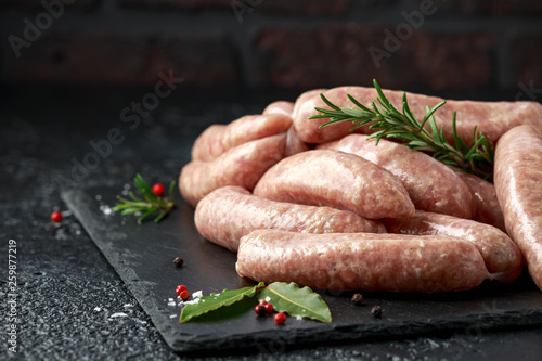 Fotografía Freshly made raw butchers sausages in skins with herbs on stone board