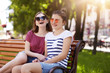 A portrait of two attractive young friends who have rest on wooden bench in local park after long walk. Laughing girls have lots of energy to continue their fun. Friend relations concept.