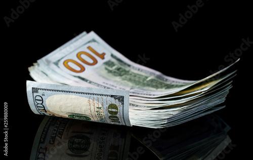 Valokuva  Heap of one hundred dollar bill on black reflective background.