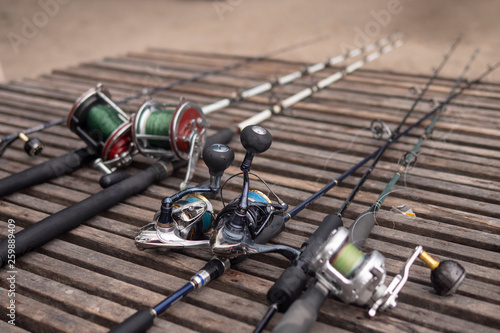 Poster Peche Fishing rods, spinning rods with fishing line on a wooden background in the morning light. Fishing.